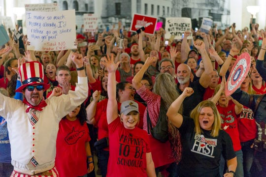 Teachers and school workers celebrate in the Capitol in West Virginia after the House of Delegates voted for an indefinite term for the controversial draft law on education on Tuesday.