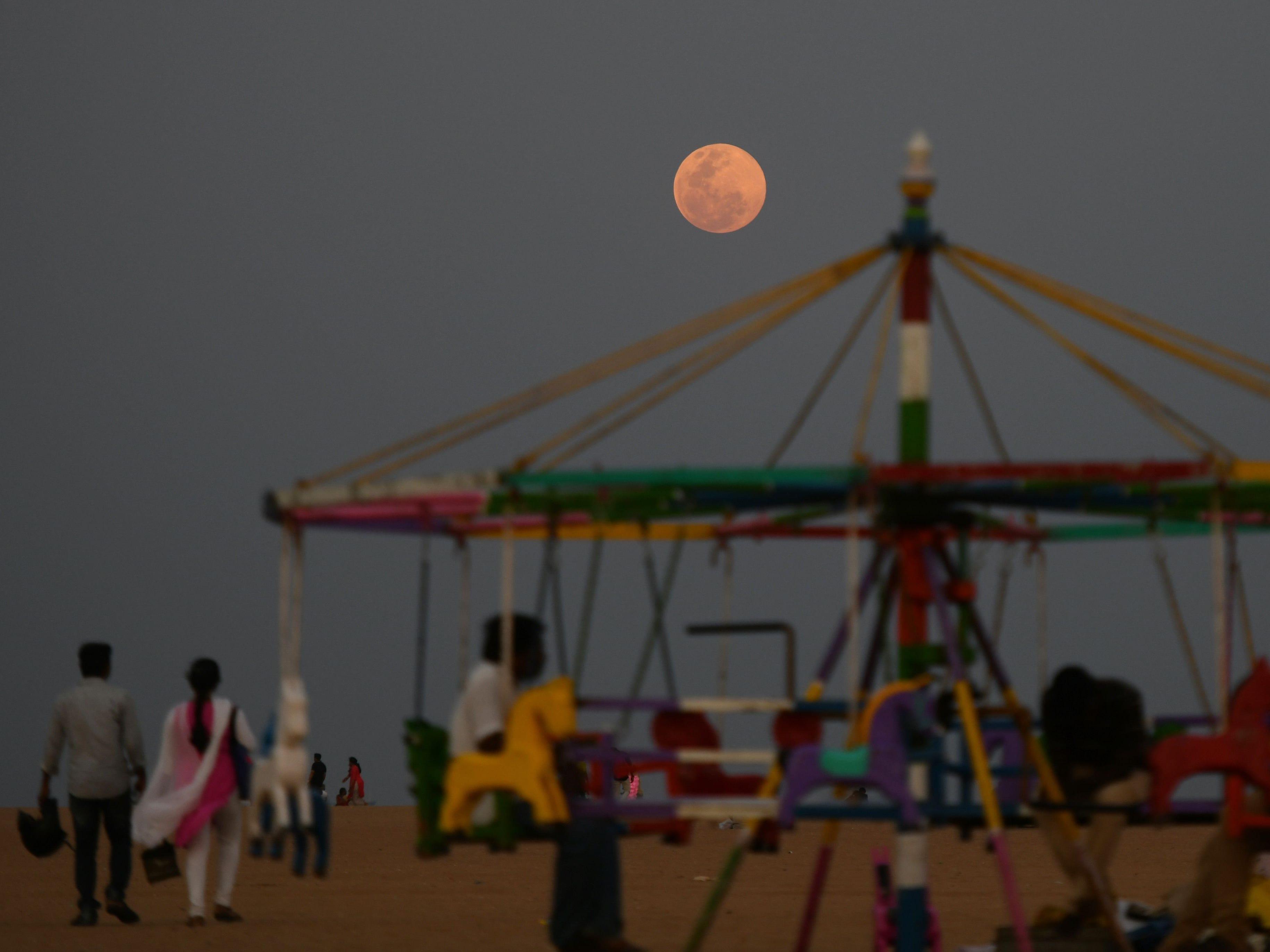 A supermoon rises as residents enjoy the evening at Marina Beach in Chennai,  India on Feb. 19, 2019.