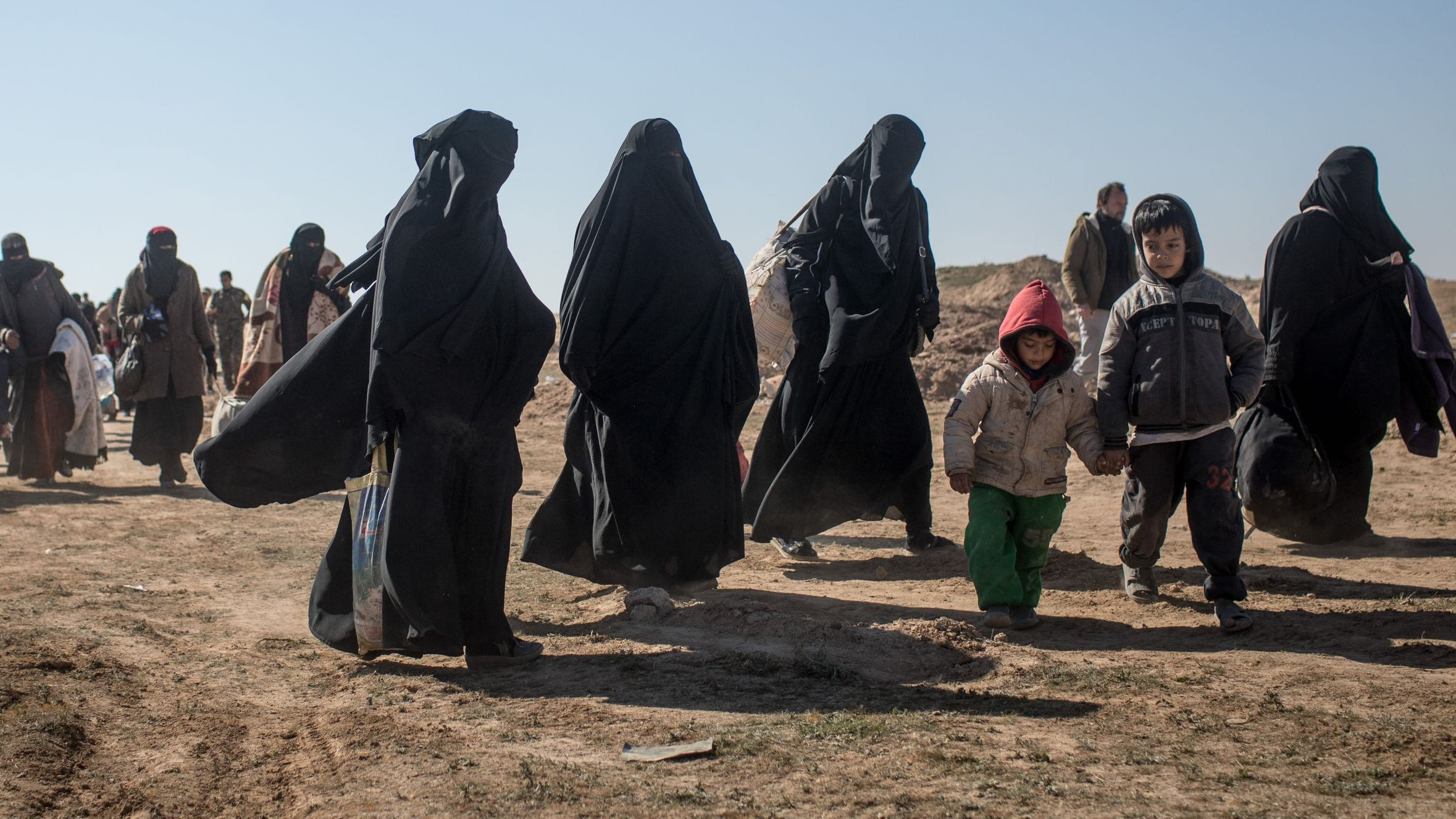 Civilians who have fled fighting in Bagouz, Syria, wait to board trucks after being screened by members of the U.S.-backed Syrian Democratic Forces in the Syrian desert on February 12, 2019.
