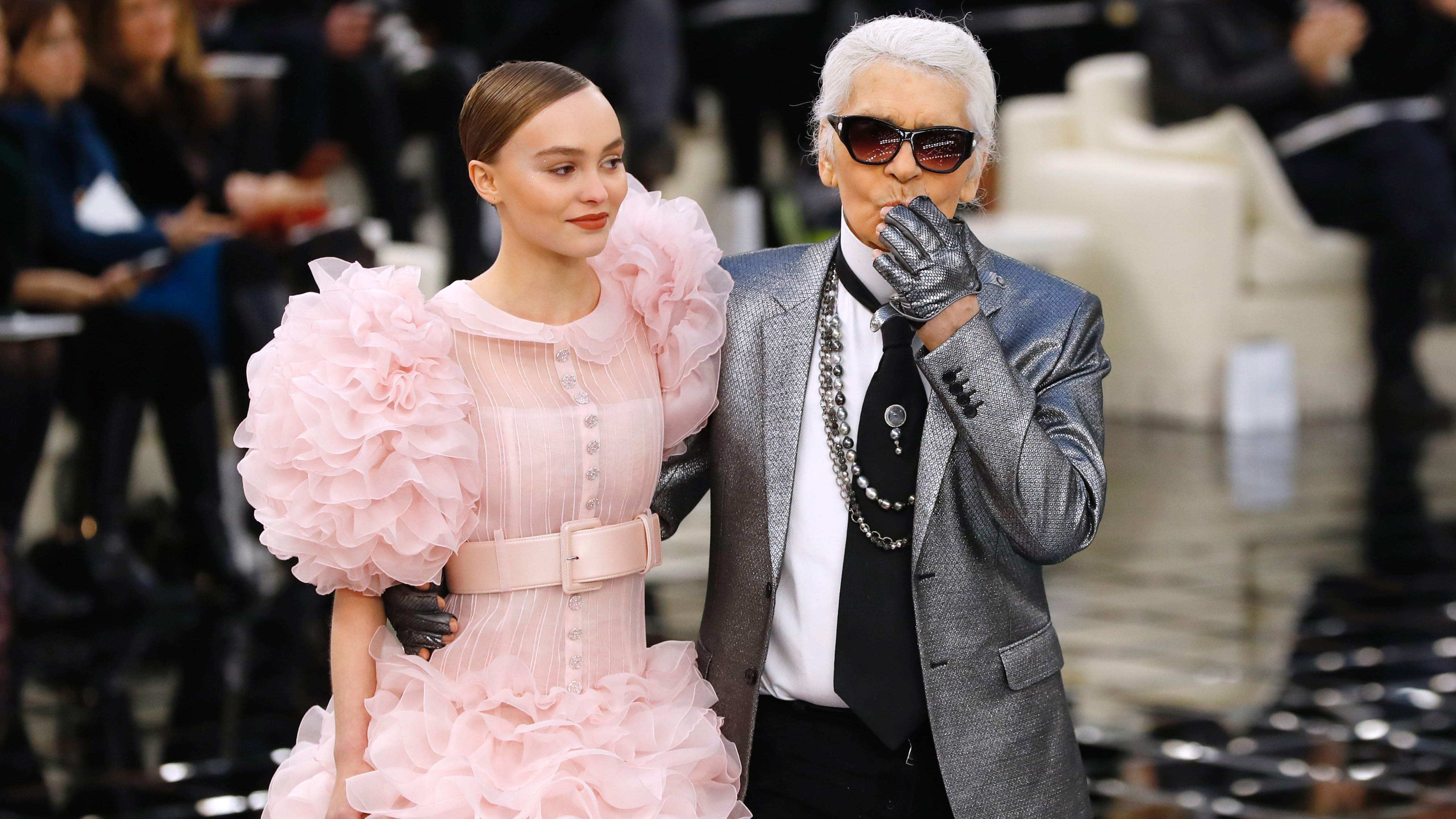 TOPSHOT - German fashion designer Karl Lagerfeld (R) acknowledges the audience next to French and US actress and model Lily-Rose Melody Depp at the end of the Chanel during the 2017 spring/summer Haute Couture collection on January 24, 2017 in Paris. / AFP PHOTO / Patrick KOVARIKPATRICK KOVARIK/AFP/Getty Images ORG XMIT: 691911991 ORIG FILE ID: AFP_KM1YK