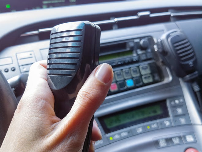 A female police officer holding a Walkie-talkie in a patrol car.