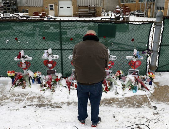A man prays at a makeshift memorial Sunday, Feb. 17, 2019, in Aurora, Ill., near Henry Pratt Co. manufacturing company where several were killed on Friday. Authorities say an initial background check five years ago failed to flag an out-of-state felony conviction that would have prevented a man from buying the gun he used in the mass shooting in Aurora.