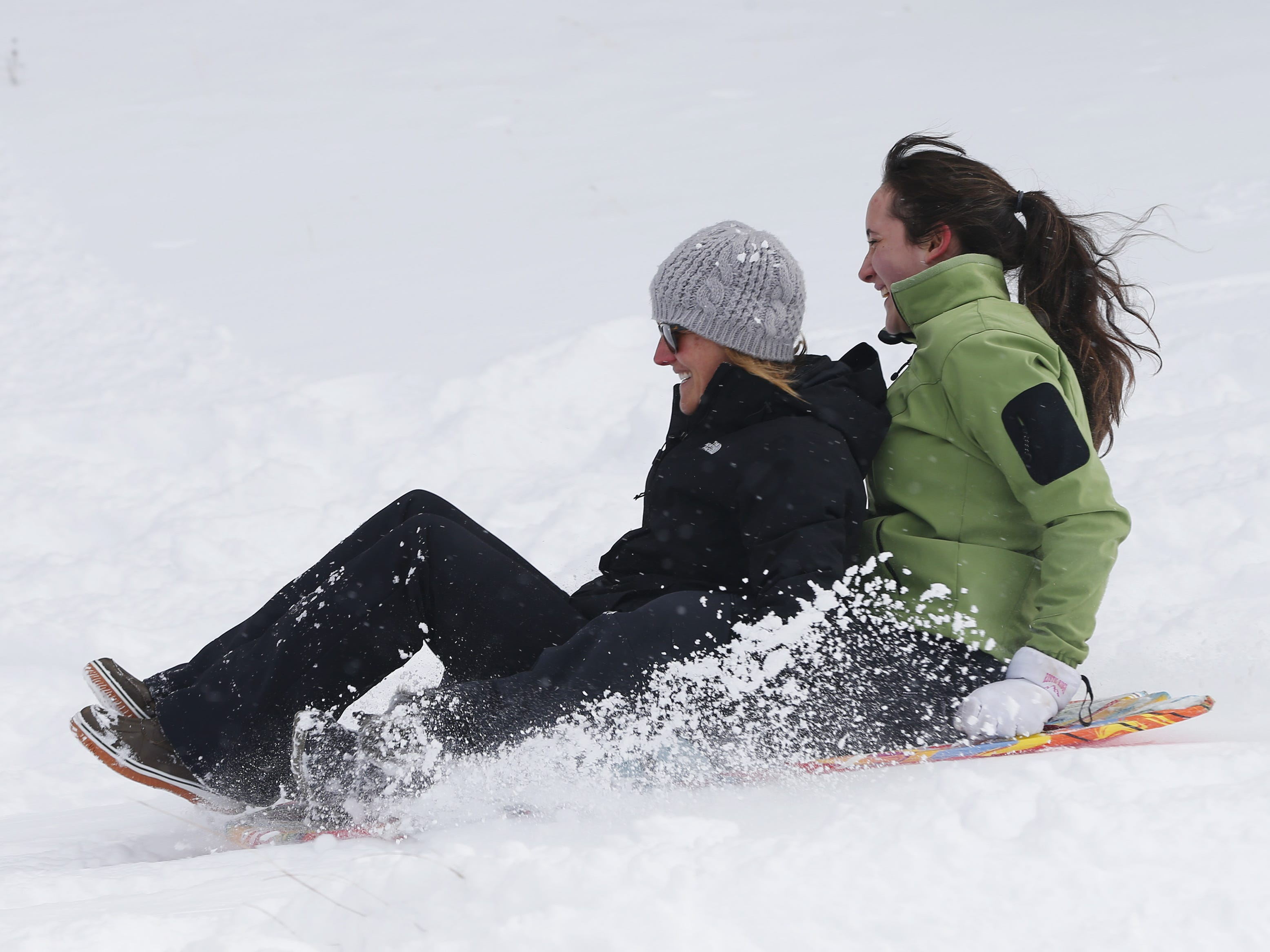K.C., left, and Noe Rhon sled down a hill in Flagstaff, Ariz. Feb. 18, 2019.