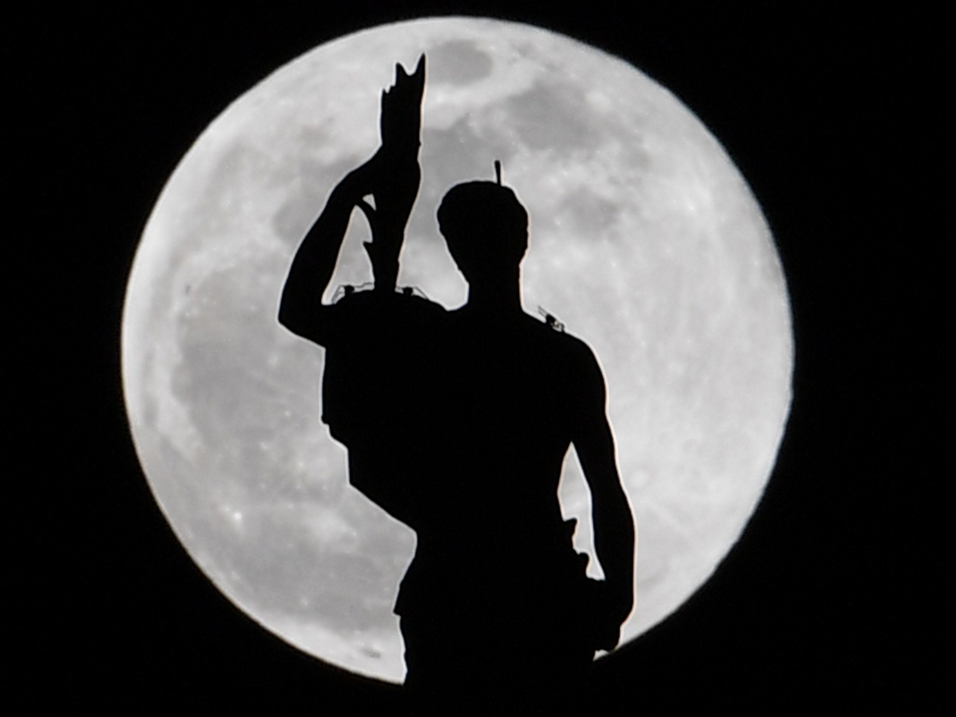 A supermoon silhouettes a statue on Duomo Cathedral in Milan, Italy on Feb. 19, 2019.