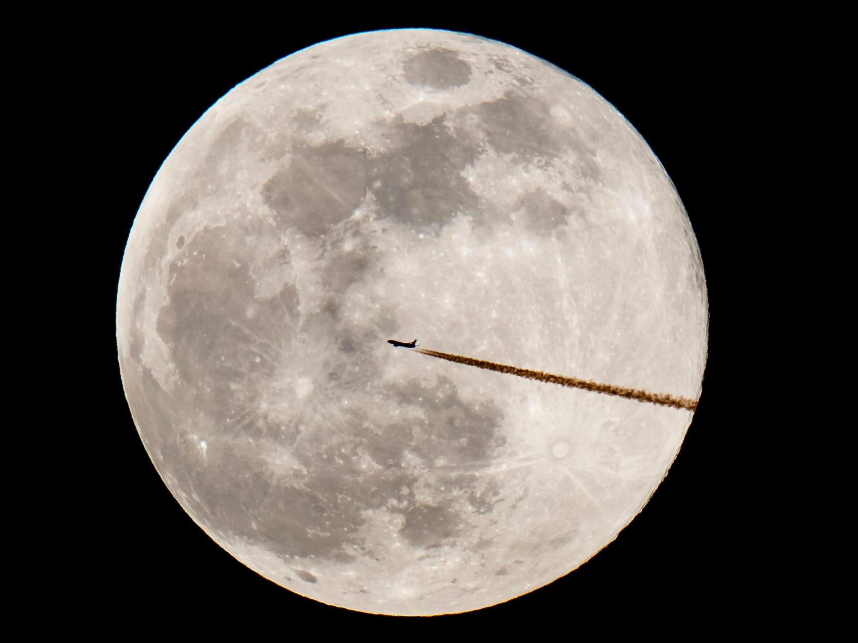 A plane flies in front of a supermoon on Feb.19, 2019, in Nuremberg, Germany.