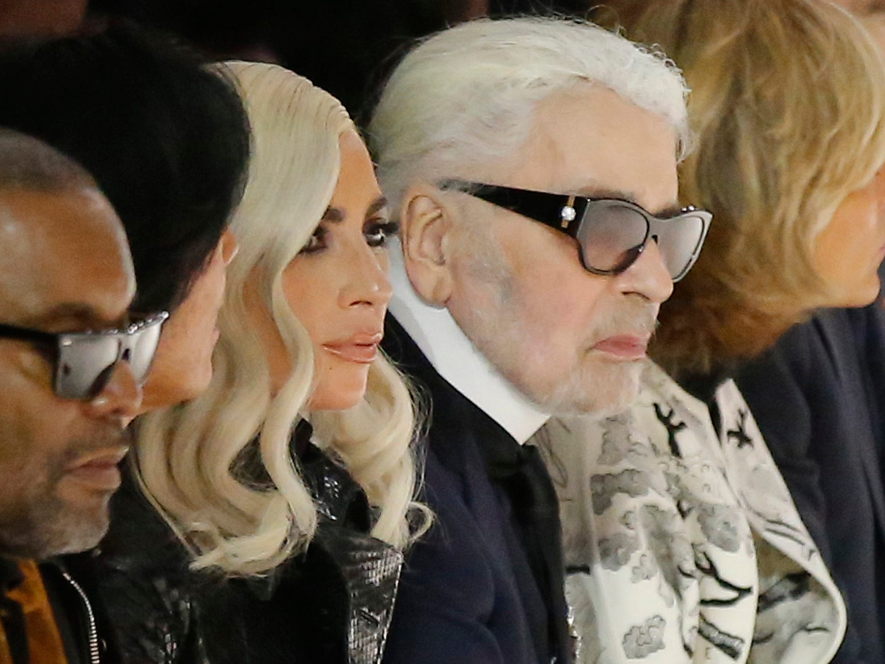 Singer Lady Gaga, centre, and designer Karl Lagerfeld, right, watch the Celine Spring/Summer 2019 ready to wear fashion collection presented in Paris, Friday, Sept. 28, 2018. (AP Photo/Michel Euler) ORG XMIT: LENT137
