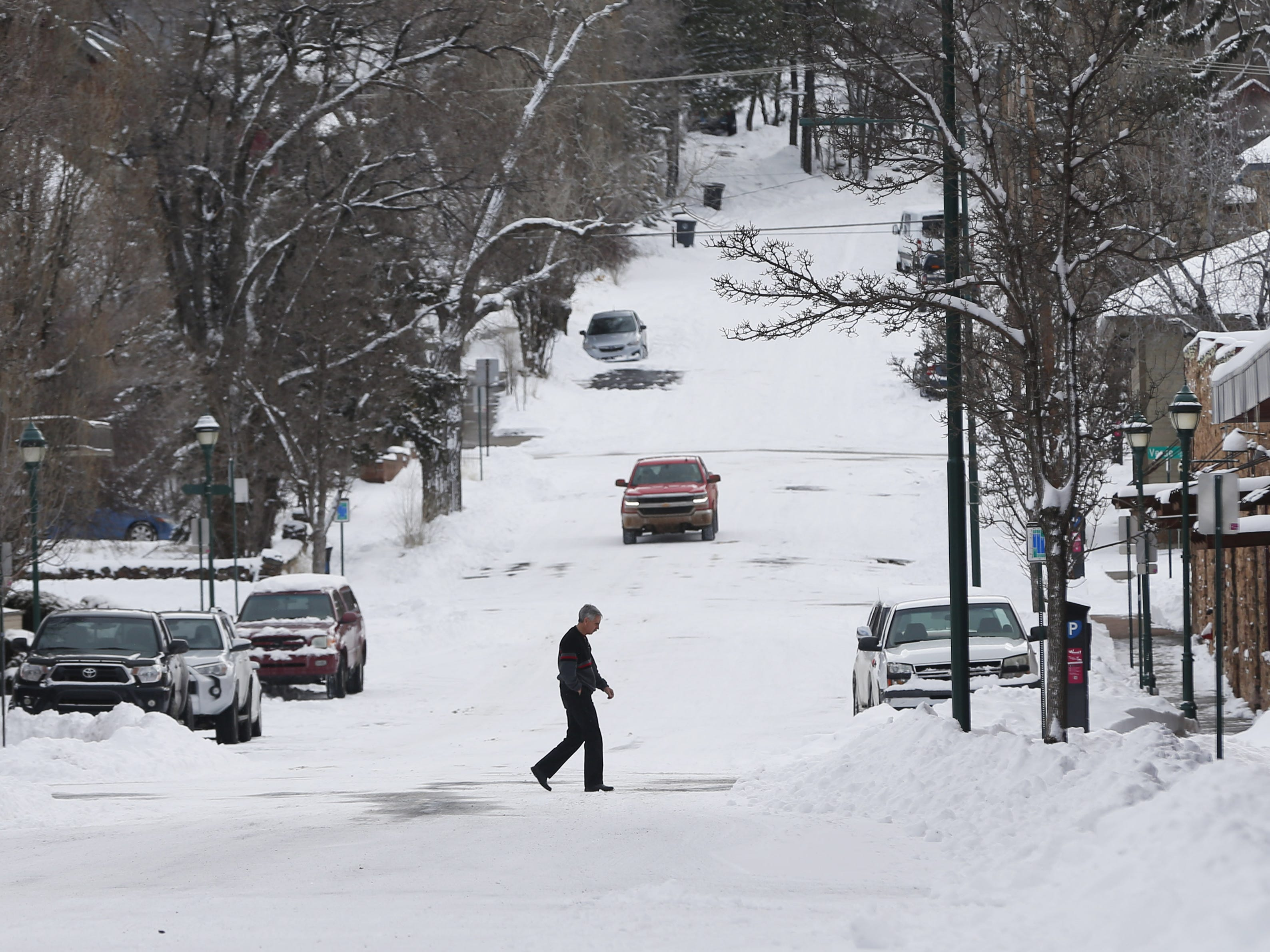 A pedestrian walks in the snow in downtown Flagstaff, Ariz. on Feb. 18, 2019.