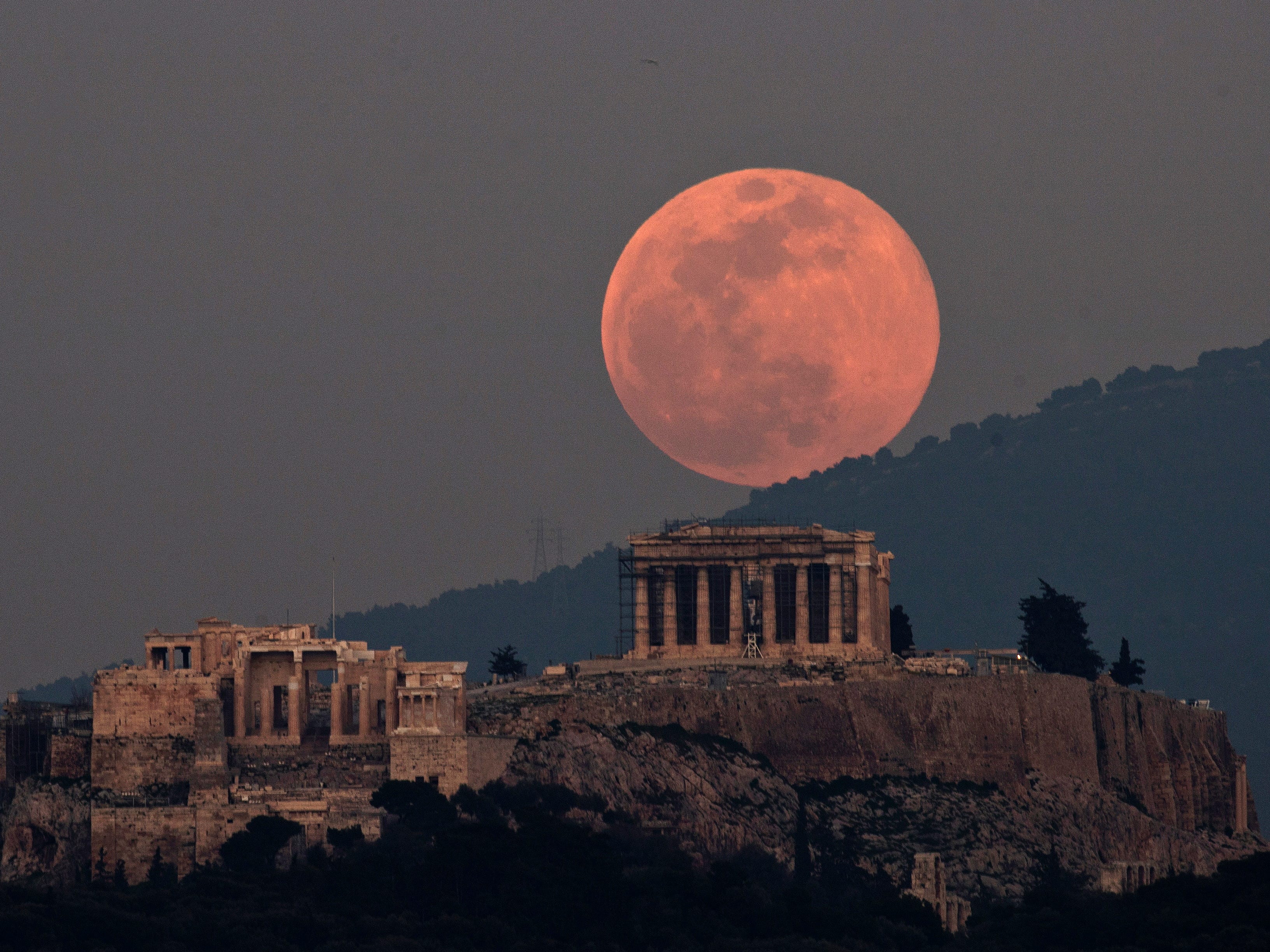 A supermoon rises over the Parthenon on the ancient Acropolis Hill in Athens, Greece, on Feb. 19, 2019.