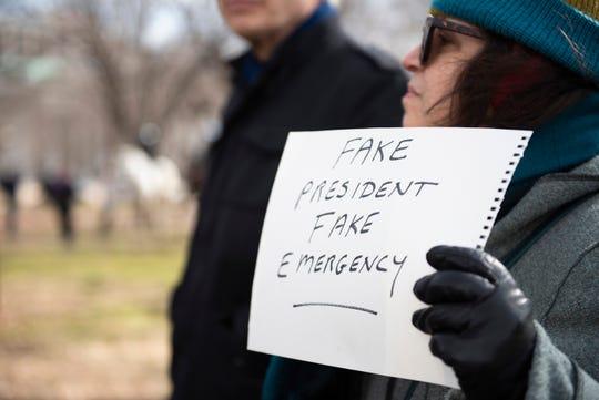 Una mujer protesta por la declaratoria de emergencia de Donald Trump.