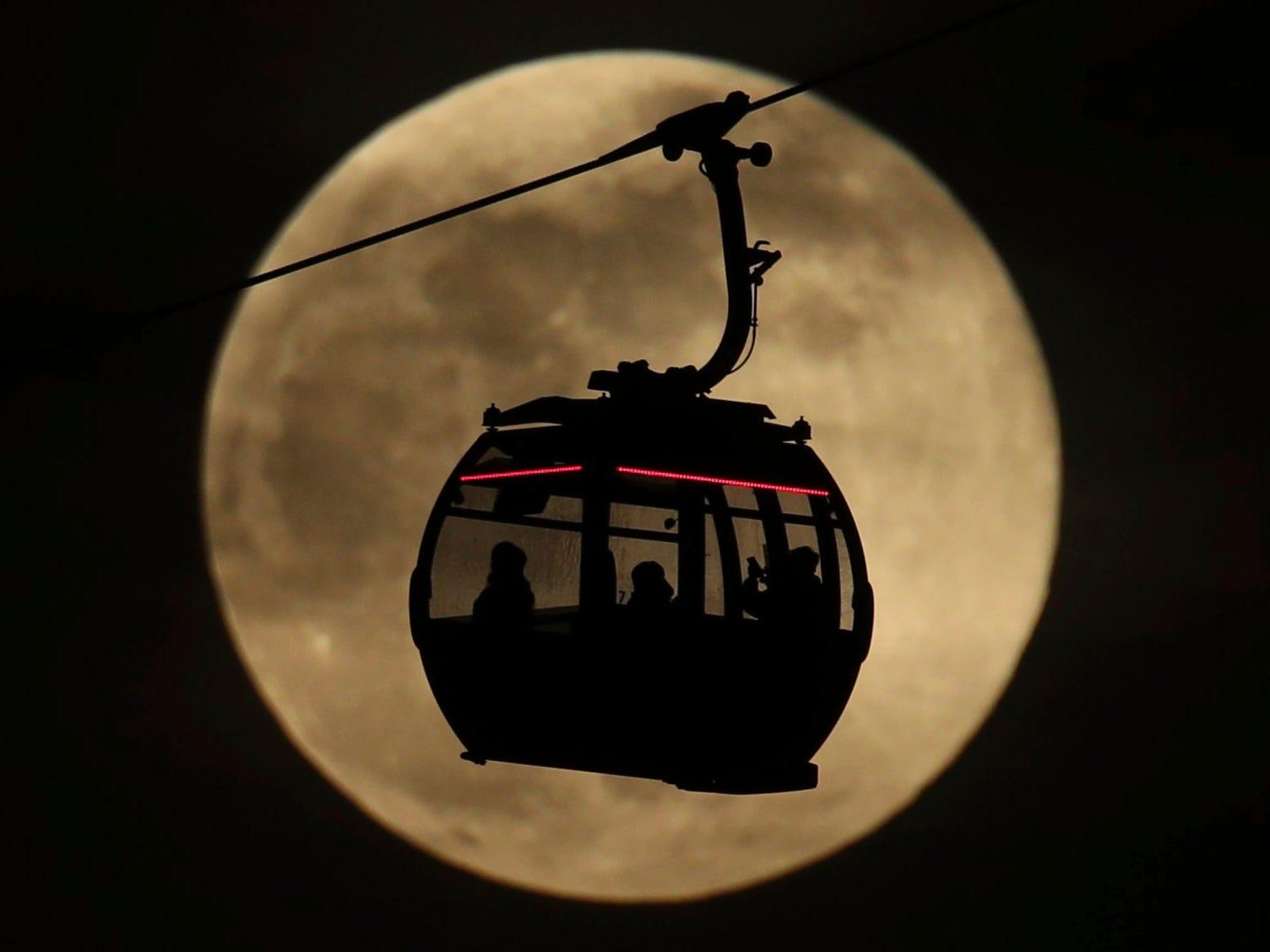 """An Emirates Air Line cable cars is silhouetted against the backdrop of the supermoon in Greenwich, London on Feb. 19, 2019. On Tuesday, the moon will """"only"""" be about 221,000 miles from Earth, which is about 17,000 miles closer than average."""
