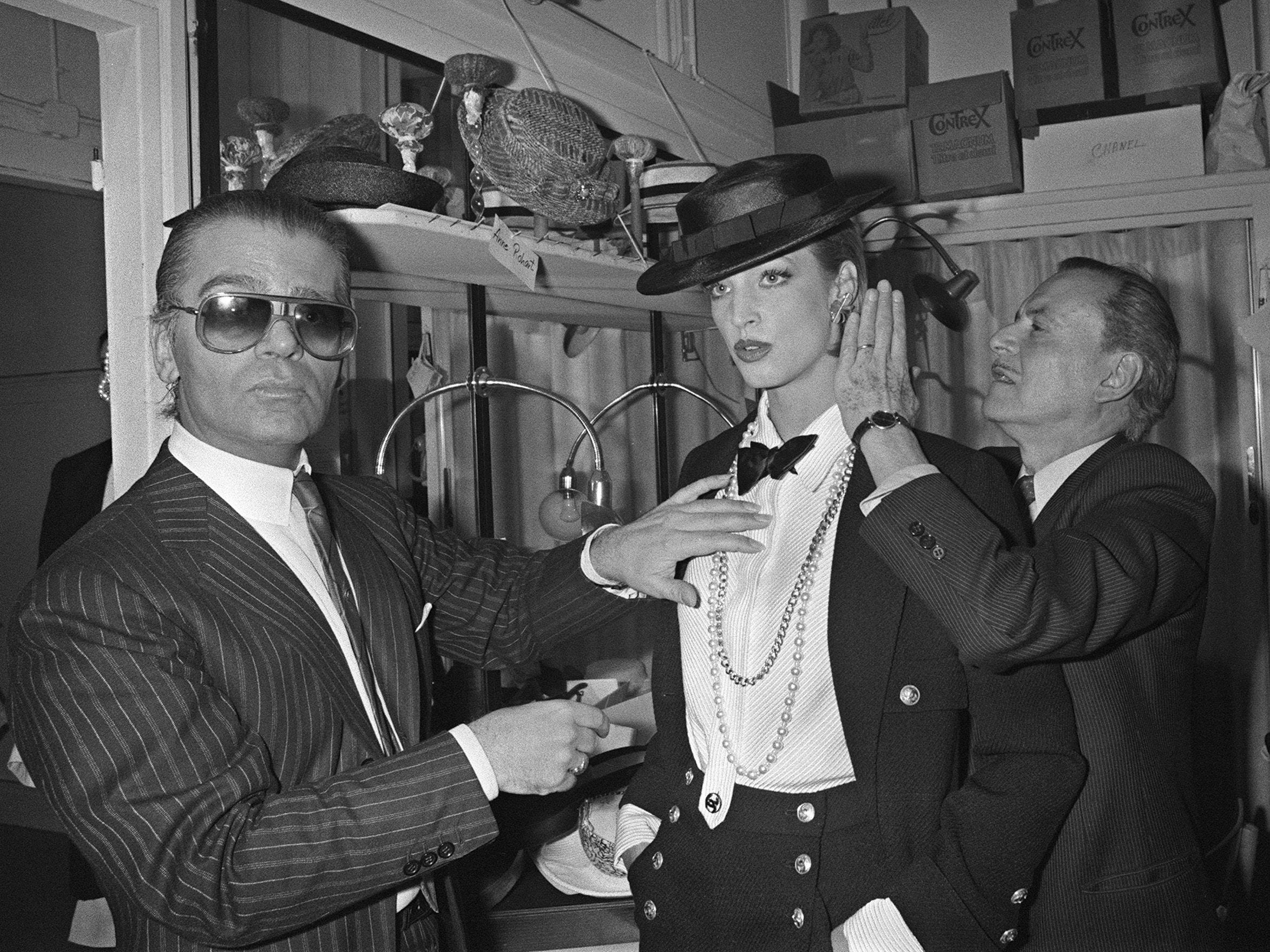 Karl Lagerfeld (L) and harstylist Alexandre (R) adjust a model's outfit during his 1st Chanel's Spring-Summer collection on Jan. 24, 1983.