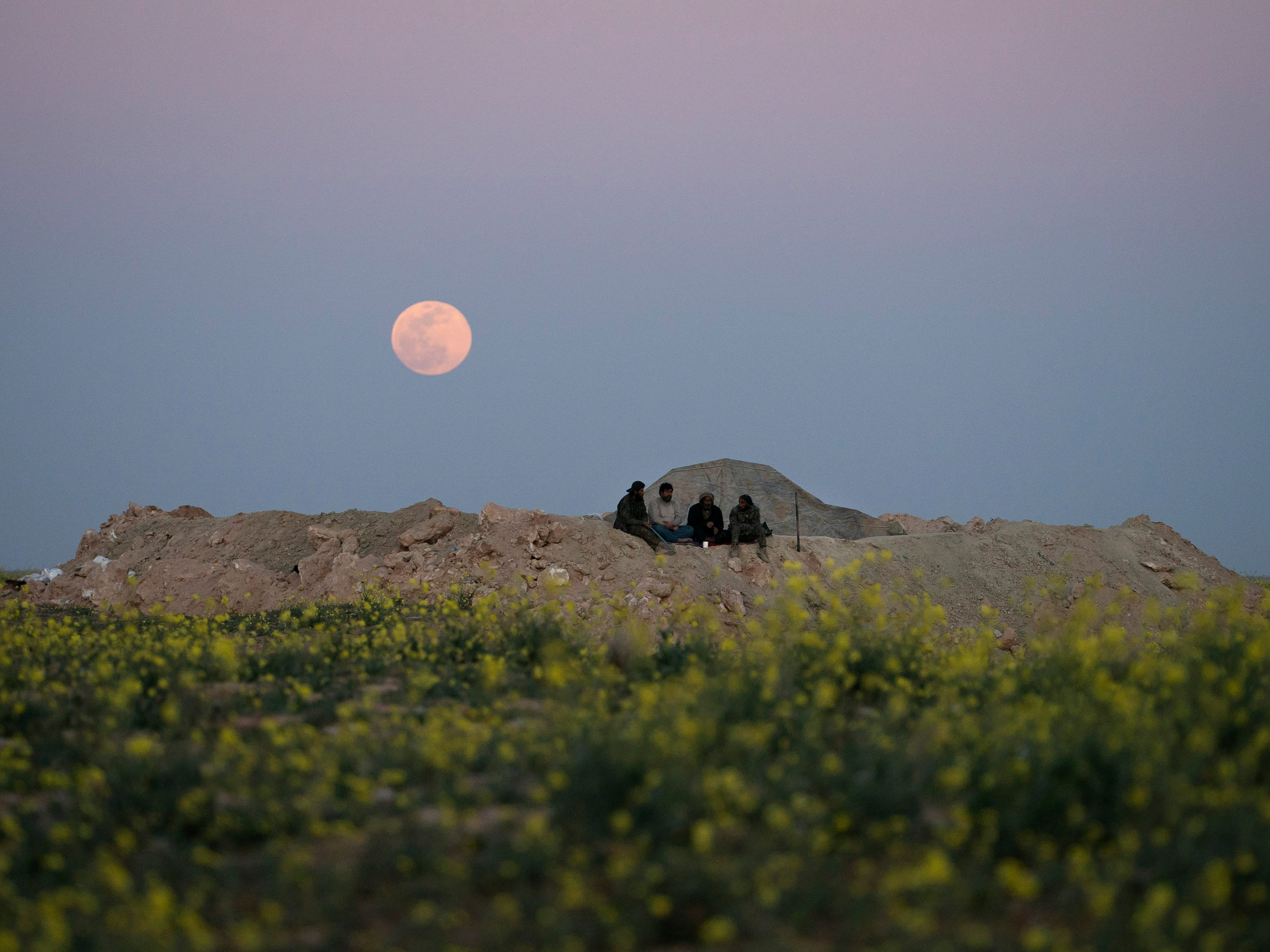 A supermoon rises behind U.S. backed Syrian Democratic Forces fighters at a defense post in the desert near the last land still held by Islamic State militants outside Baghouz, Syria, on  Feb. 19, 2019.