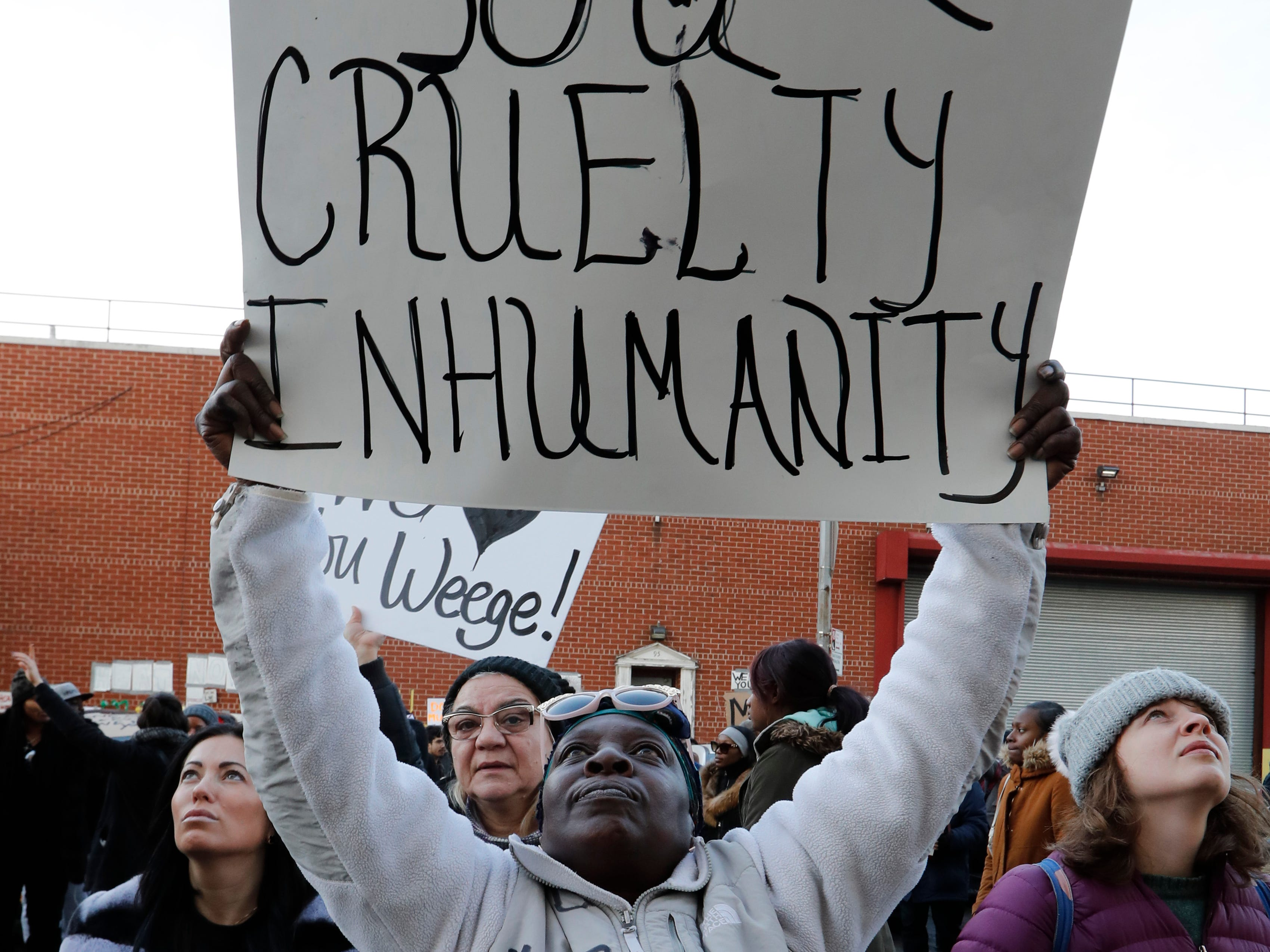 Caren Burton, of Bayshore, Long Island, holds a sign so her incarcerated son Tyrone Robinson can see it as she protests jail conditions from outside the Metropolitan Detention Center. Inmates were without heat, hot water, electricity and sanitation for several days.