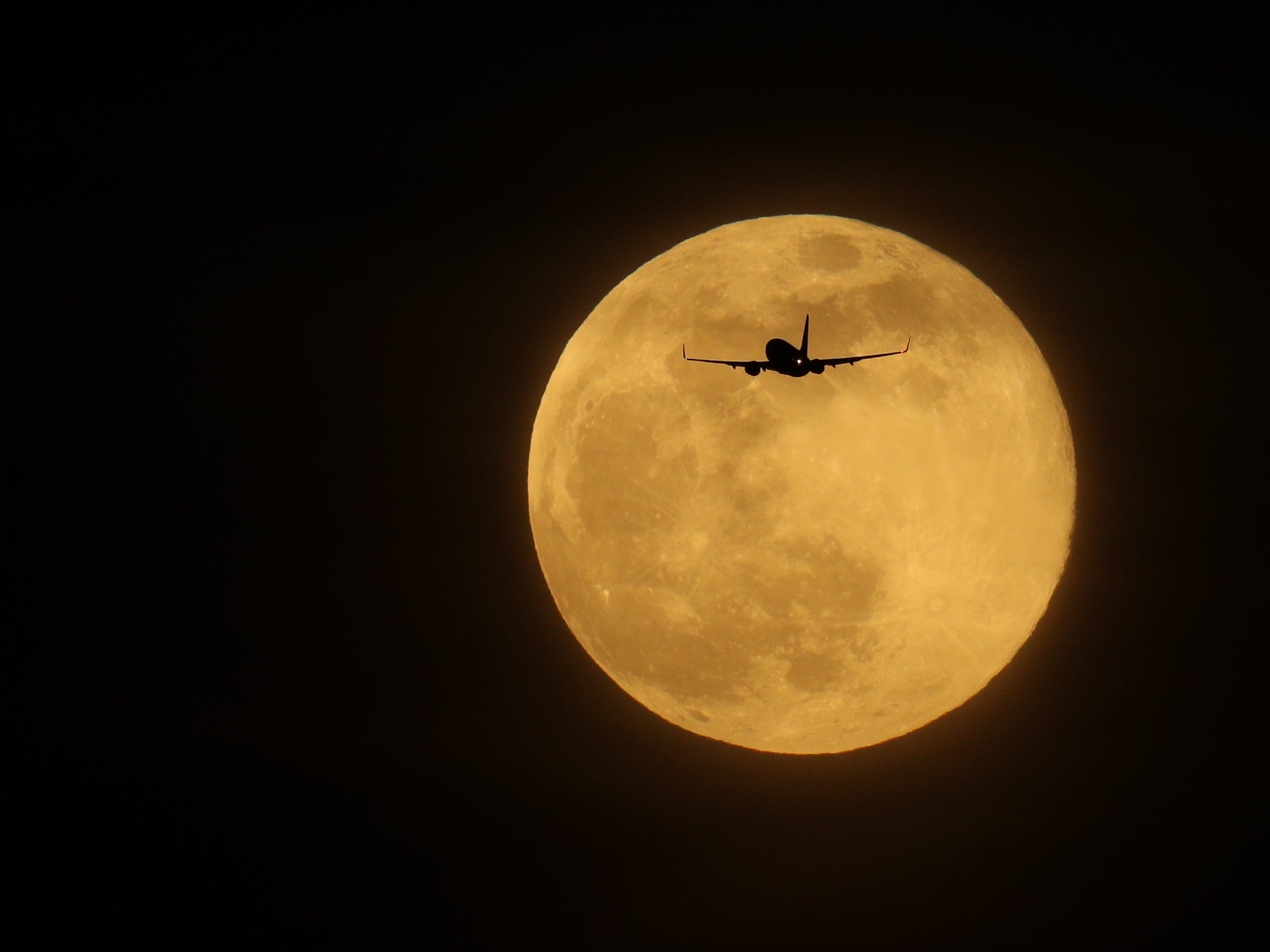 A plane flies in front of a supermoon on Feb. 19, 2019, in London.