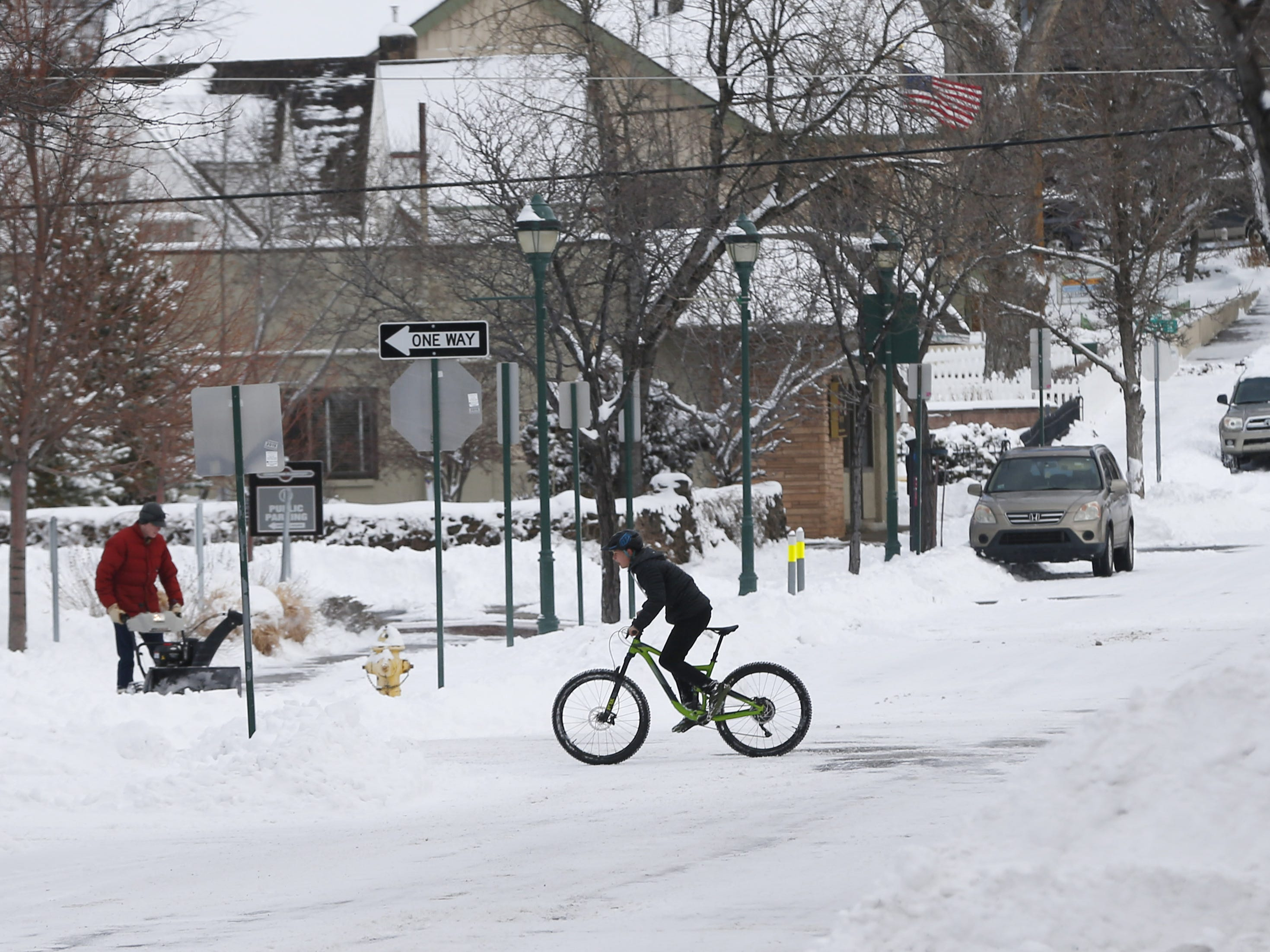 A cyclist rides his bike in downtown Flagstaff, Ariz. on Feb. 18, 2019.