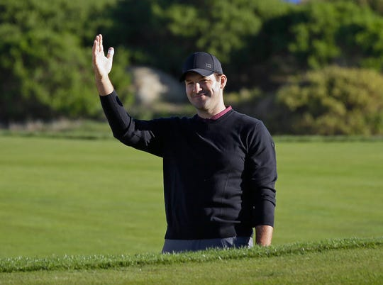 Tony Romo waves after hitting the ball out of a bunker and close to the pin on the 11th green of the Monterey Peninsula Country Club Shore Course during the second round of the AT&T Pebble Beach National Pro-Am golf tournament, in Pebble Beach, California.