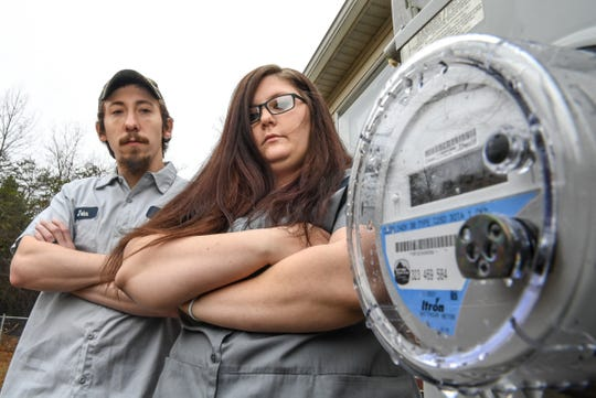 John Hawkins and Tabitha Riley look at the 'smart meter' at their home in Dacusville. Riley said their power bill rose dramatically after Blue Ridge Electric Cooperative installed the meter last year.