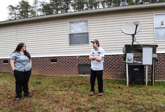 "Tabitha Riley and her fiancŽ John Hawkins of Dacusville stand near the Blue Ridge Electric ""smart"" meter at their home Monday. Riley said the power bill rose dramatically after the new meter was installed at the residence."