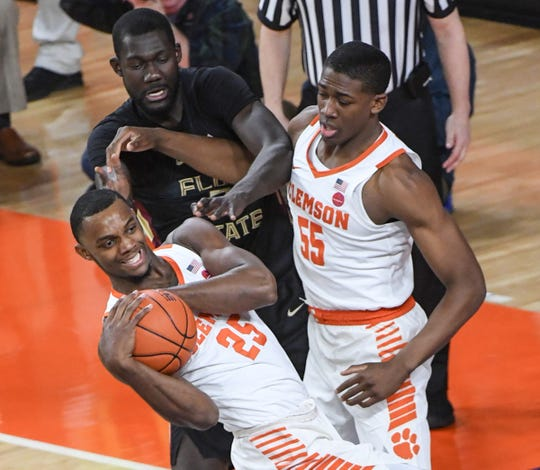 Clemson forward Aamir Simms (25) rebounds near teammate Clemson center Trey Jemison (55) and Florida State center Christ Koumadje(21) during the first half at Littlejohn Coliseum in Clemson Tuesday, February 19, 2019.