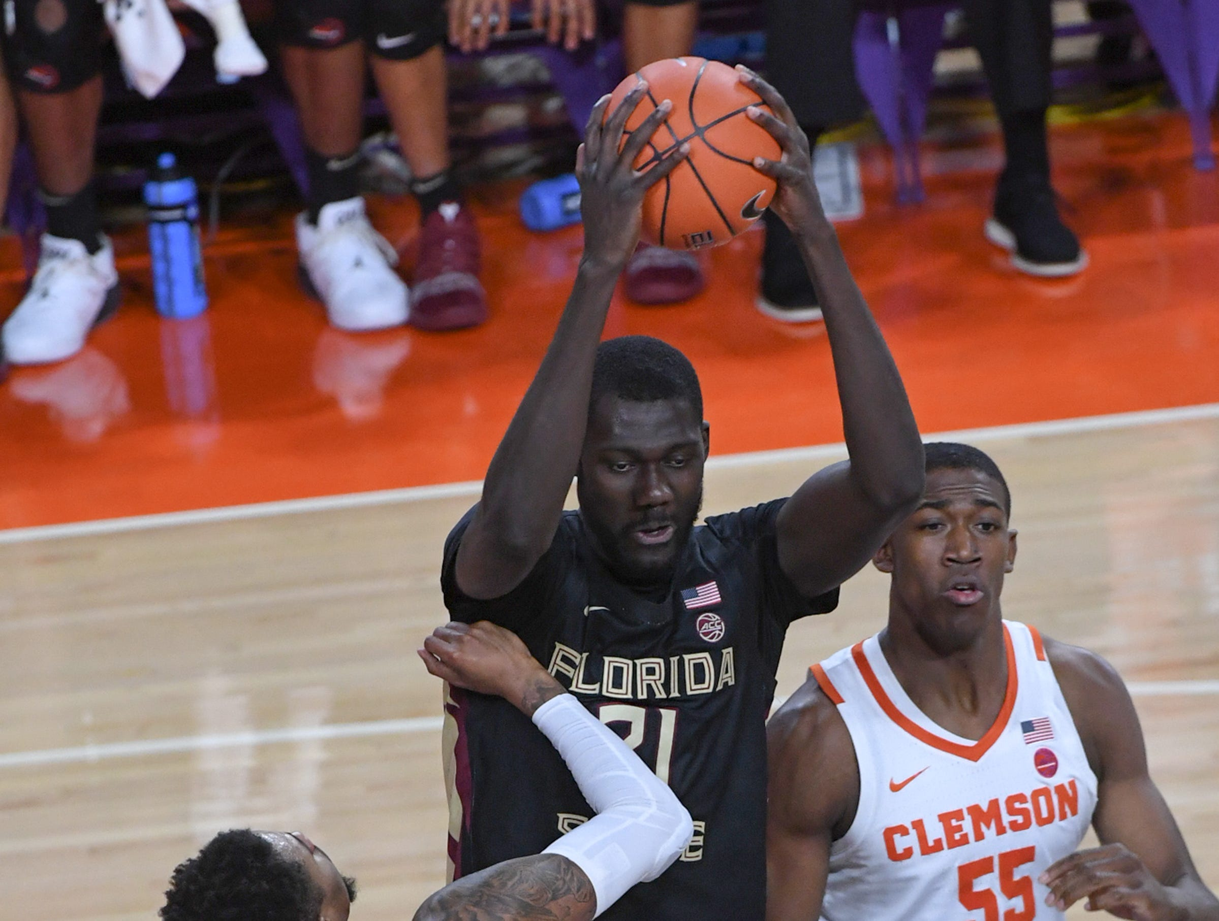 Clemson guard Shelton Mitchell (4) watches Florida State center Christ Koumadje(21) rebound during the first half at Littlejohn Coliseum in Clemson Tuesday, February 19, 2019.