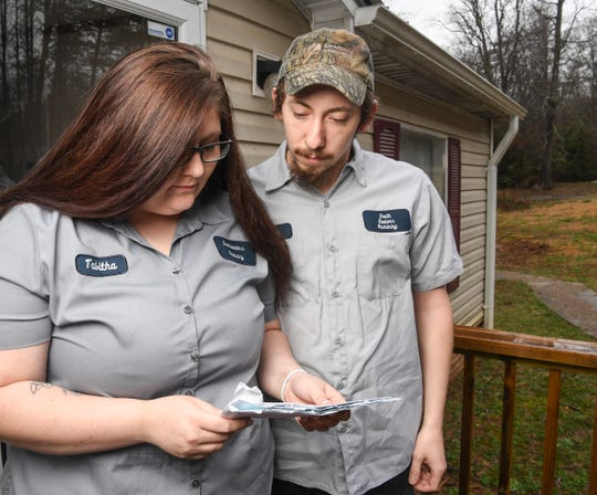 Tabitha Riley and John Hawkins of Dacusville looks at the power bill from Blue Ridge Electric Monday. Riley and Hawkins say their bill rose dramatically after a smart meter was installed at their residence.