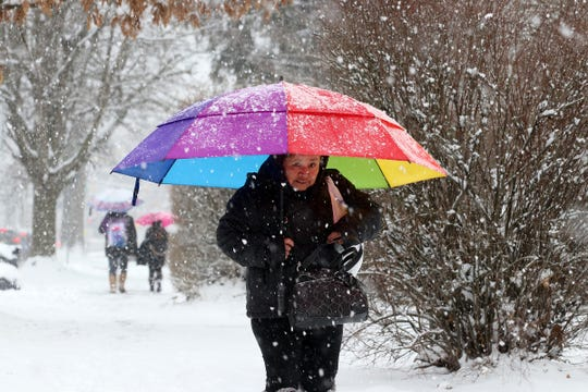 Blanca Pilar of Freehold protects herself from the snow with an umbrella as she walks along Broadway in Freehold, NJ Wednesday, February 20, 2019.