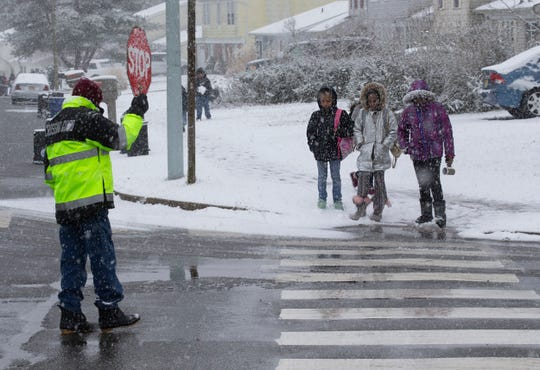 Crossing Guard Harold Roberts stops cars to allow walkers from the Donohue School to cross Village Drive on their way home after early dismissal due to the snow in Barnegat on February 20, 2019.