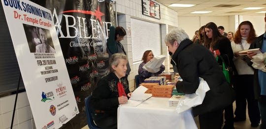 "Temple Grandin signs copies of her books at the Region 14 Education Service Center's ""Autism Extravaganza."""