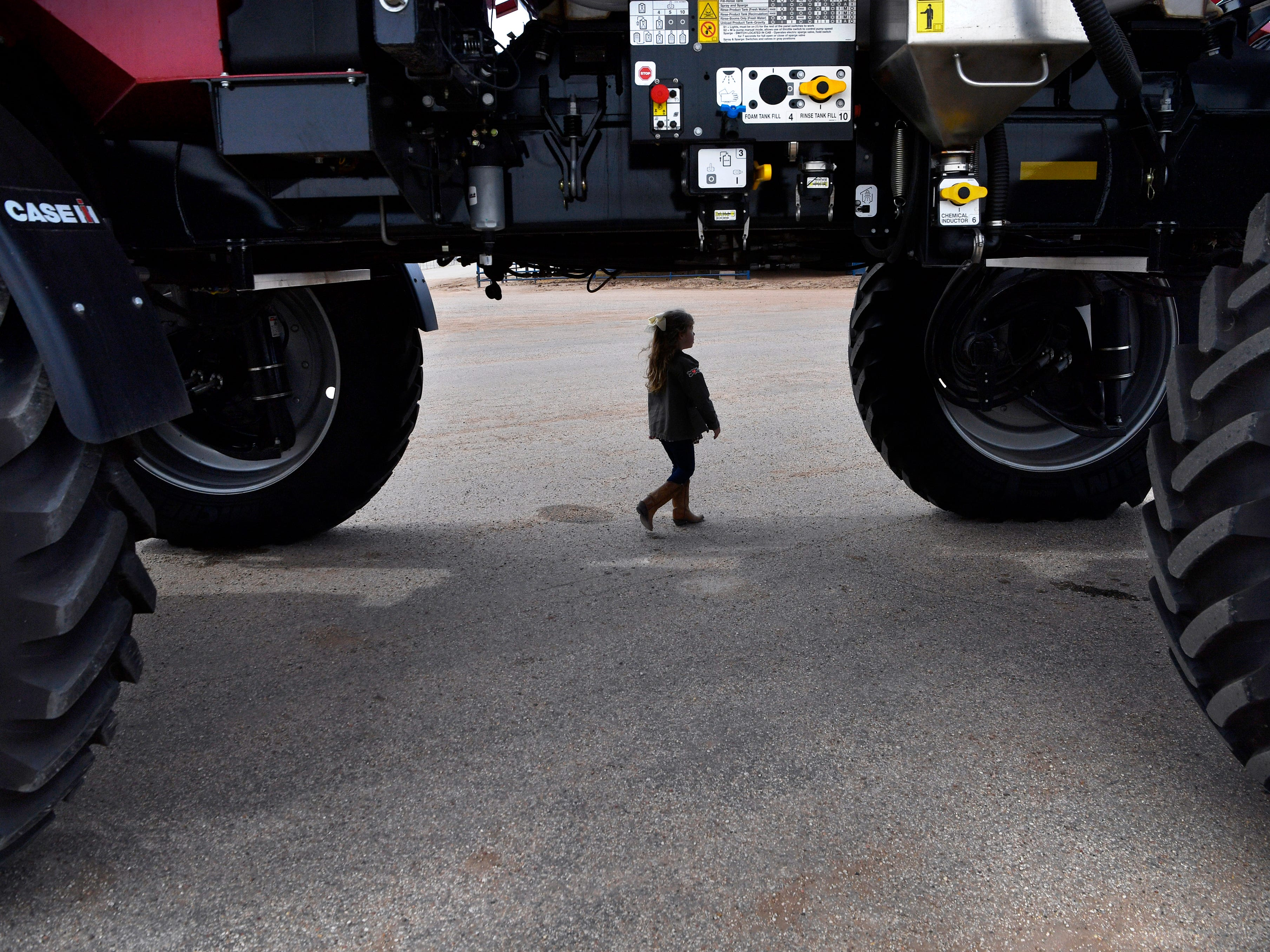 Lennon Holloway, 5, walks under a farm sprayer as she follows her grandfather, Paul Holloway and her three-year-old brother Carson during Wednesday's Farm-Ranch-Wildlife Expo at the Taylor County Expo Center Feb. 20, 2019.