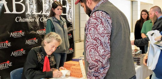 Temple Grandin signs copies of her books at the Taylor County Expo Center Wednesday.