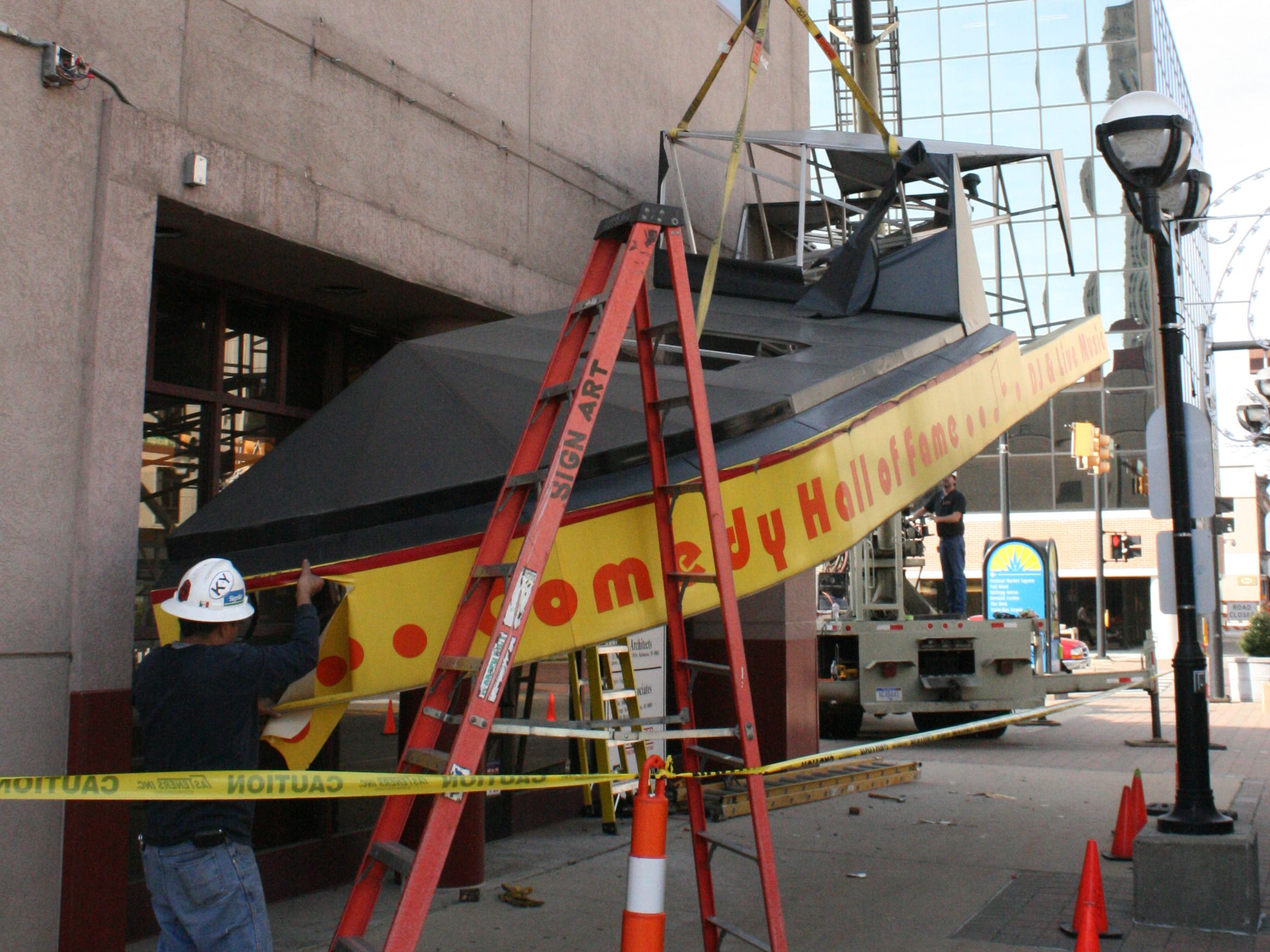 Crews dismantle the marquee from the old Gary Fields Comedy Club on West Michigan Avenue. The building now houses a branch of Kellogg Community Federal Credit Union.