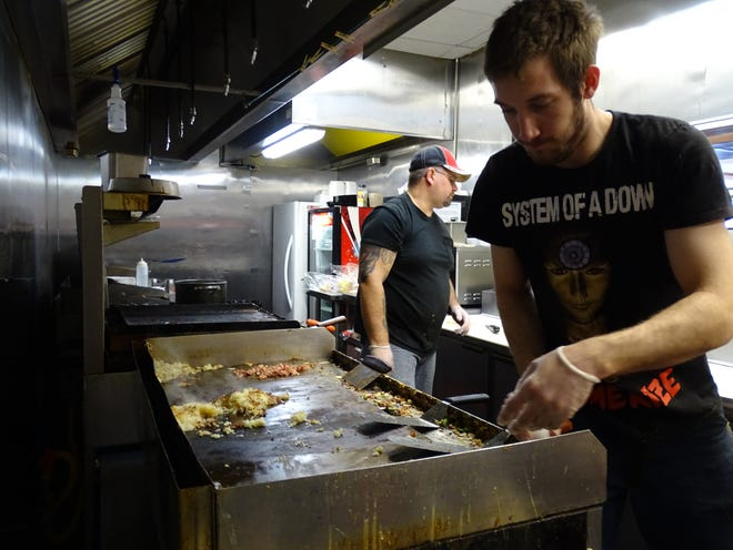 Rick Horsley and Skyle Runion, from left, work in the kitchen at Lu Lu's Kitchen on Wednesday morning.