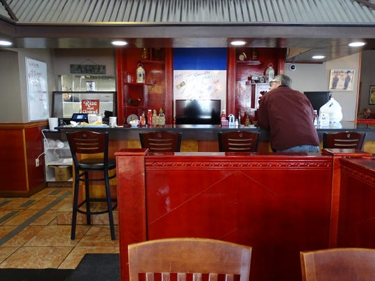A customer sits at the front counter at Lu Lu's Kitchen on Wednesday morning.