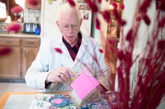 Bob Taylor works on birdhouse at his home in Mount Laurel, N.J. recently. Taylor purchases and paints custom birdhouses for cancer patients. This pink one will be donated for breast cancer patients.