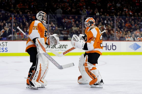 Brian Elliott, right, relieved Carter Hart after the rookie allowed three goals on nine shots in what was a poor first period for the Flyers.