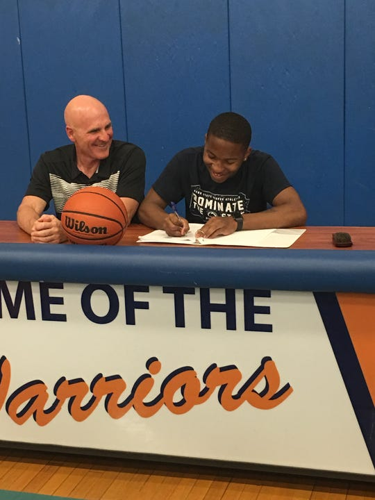 Camden Tech boys basketball coach Rob Sweeney, left, sits with 2018 graduate Zayre Kinslow as Kinslow commits to play college hoops at Penn State-Beaver.