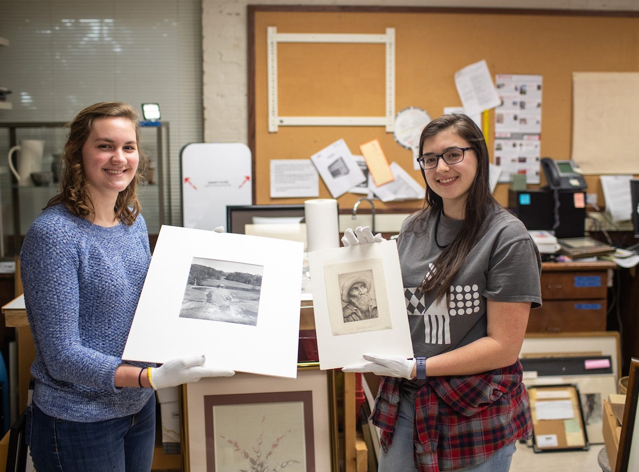 Austin Peay State University art students Sarah Potter and Katherine Tolleson hold their discoveries. Potter is holding a Philippe Halsman photo print of Winston Churchill, and Tolleson is holding a drypoint by Alphonse Legros. The works were found in Austin Peay State University's Permanent Collection.