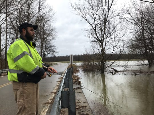 Volunteer firefighter James Madden fishes from the bridge on Lock B South as he waits on standby for any emergency callouts during flooding on Wednesday, Feb. 20, 2019.