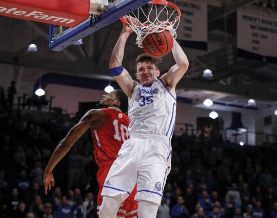 Drake senior Nick McGlynn slams a dunk ahead of Bradley sophomore Elijah Childs late in the game on Tuesday, Feb. 19, 2019, at the Knapp Center in Des Moines.
