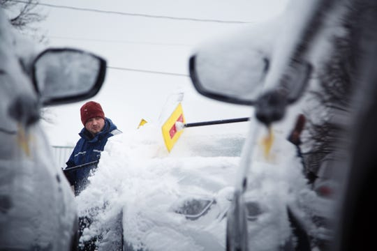 Jonathan Sanders helps clear snow off of new cars at the Charles Gabus Ford dealership as another round of winter weather passes through on Wednesday, Feb. 20, 2019 in Des Moines.