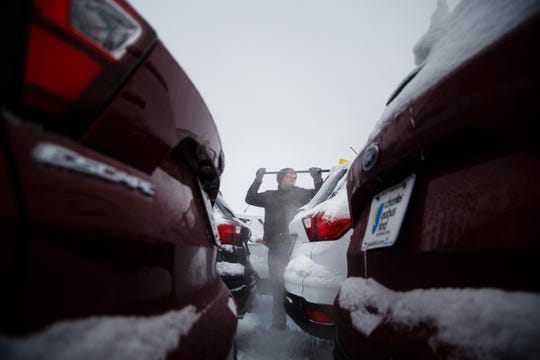 Anthony Graham helps clear snow off of new cars at the Charles Gabus Ford dealership as another round of winter weather passes through on Wednesday, Feb. 20, 2019 in Des Moines.