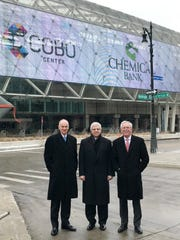 Thomas Shafer, president and CEO of Chemical Bank, Gary Torgow, chairman of the board of the Chemical Financial Corp. and David Provost, president and CEO of the Chemical Financial Corp. stand  before Detroit's convention center.