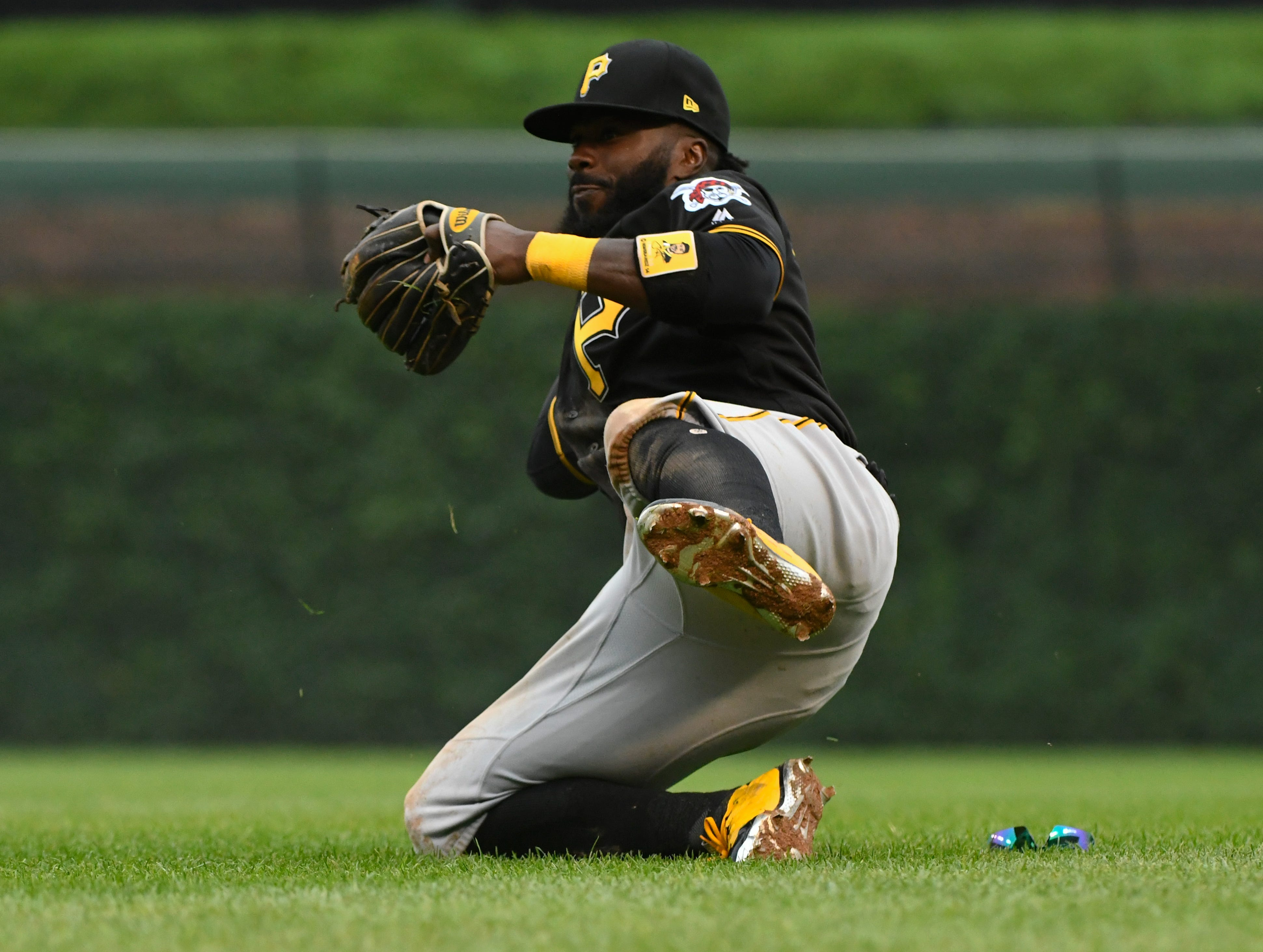 Pittsburgh Pirates second baseman Josh Harrison stops a ball hit by Chicago Cubs' Anthony Rizzo during the ninth inning of a baseball game on Sunday, June 10, 2018, in Chicago.