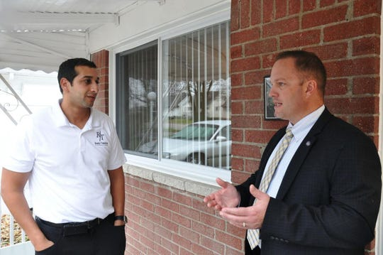 Shady Awad, left, and Taylor Mayor Rick Sollars discuss a partnership to rehabilitate foreclosed homes in the downriver community.