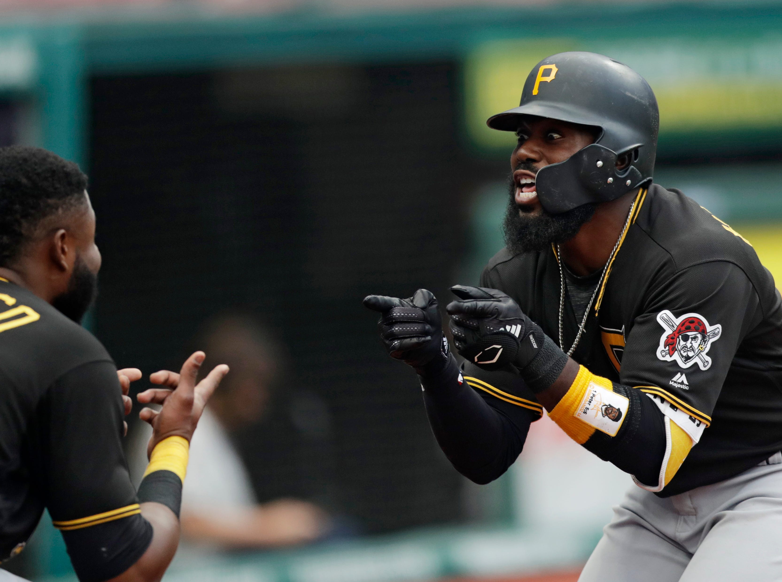 Pittsburgh Pirates' Josh Harrison, right, celebrates with Gregory Polanco after hitting a three-run home run in the second inning of a baseball game against the Cleveland Indians, Monday, July 23, 2018, in Cleveland.