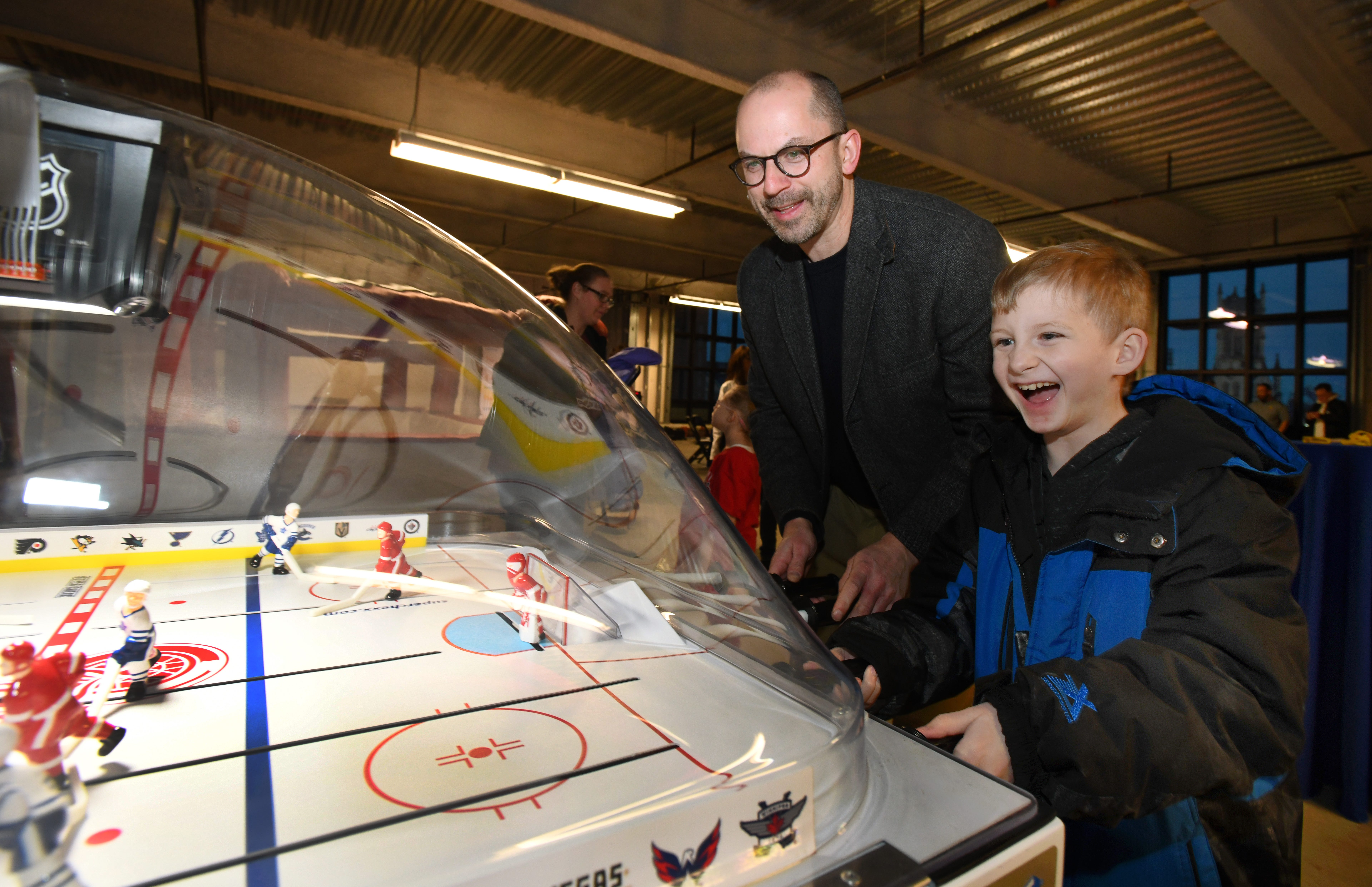 Retired Detroit Red Wing Jason Woolley plays bubble hockey with Alexander Swann, 9, during the Children's Miracle Network event at Little Caesar's Arena.