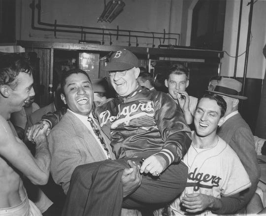 Brooklyn Dodgers pitcher Don Newcombe, second from left, holds up Dodgers manager Burt Shotton in the Dodgers dressing room after they won the National League pennant against the Philadelphia Phillies, in Philadelphia, October 2, 1949.