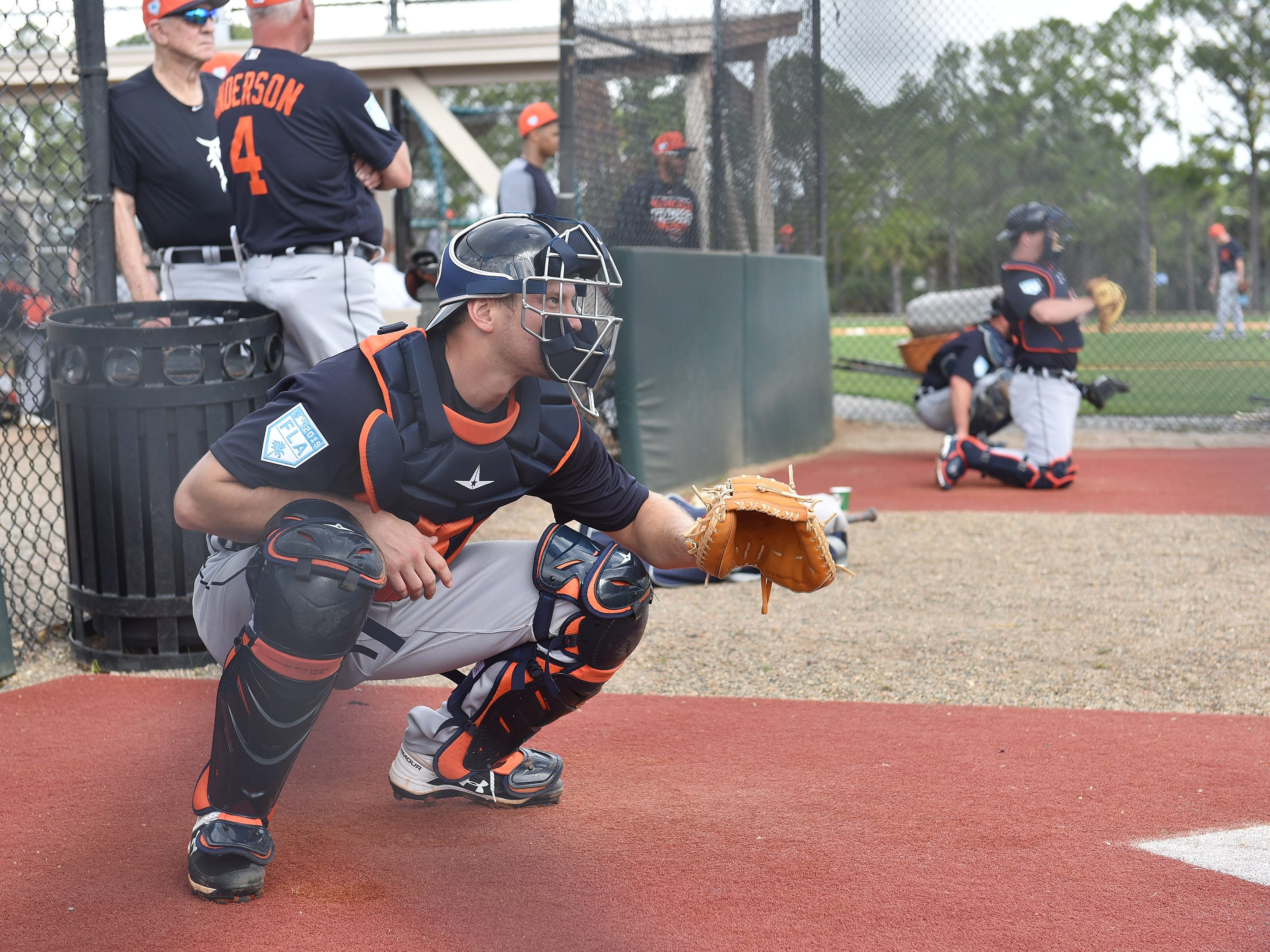 Tigers catcher John Hicks catches a bullpen session.