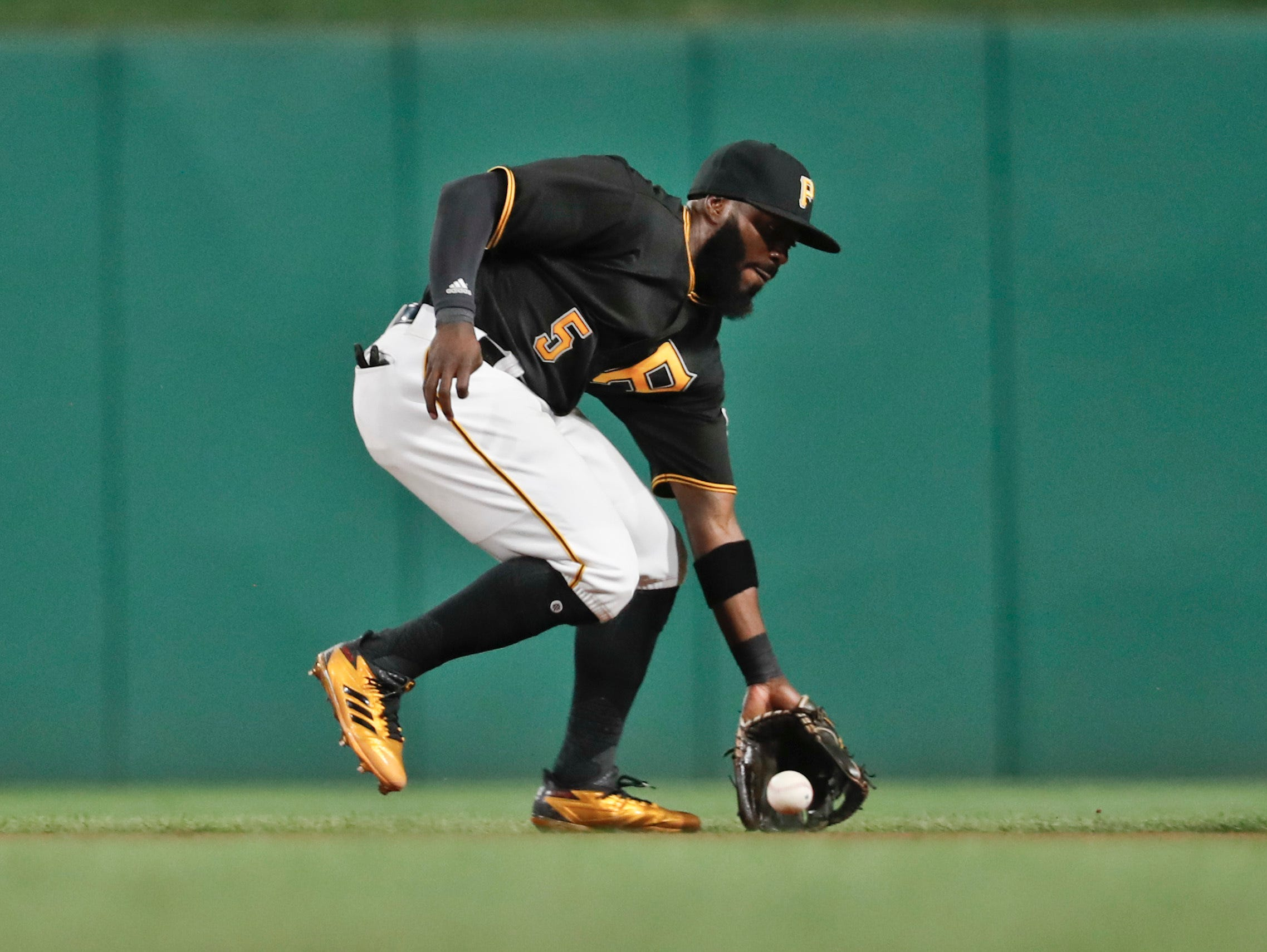 Pittsburgh Pirates second baseman Josh Harrison fields a ground ball against the St. Louis Cardinals in a baseball game, Saturday, Aug. 4, 2018, in Pittsburgh.