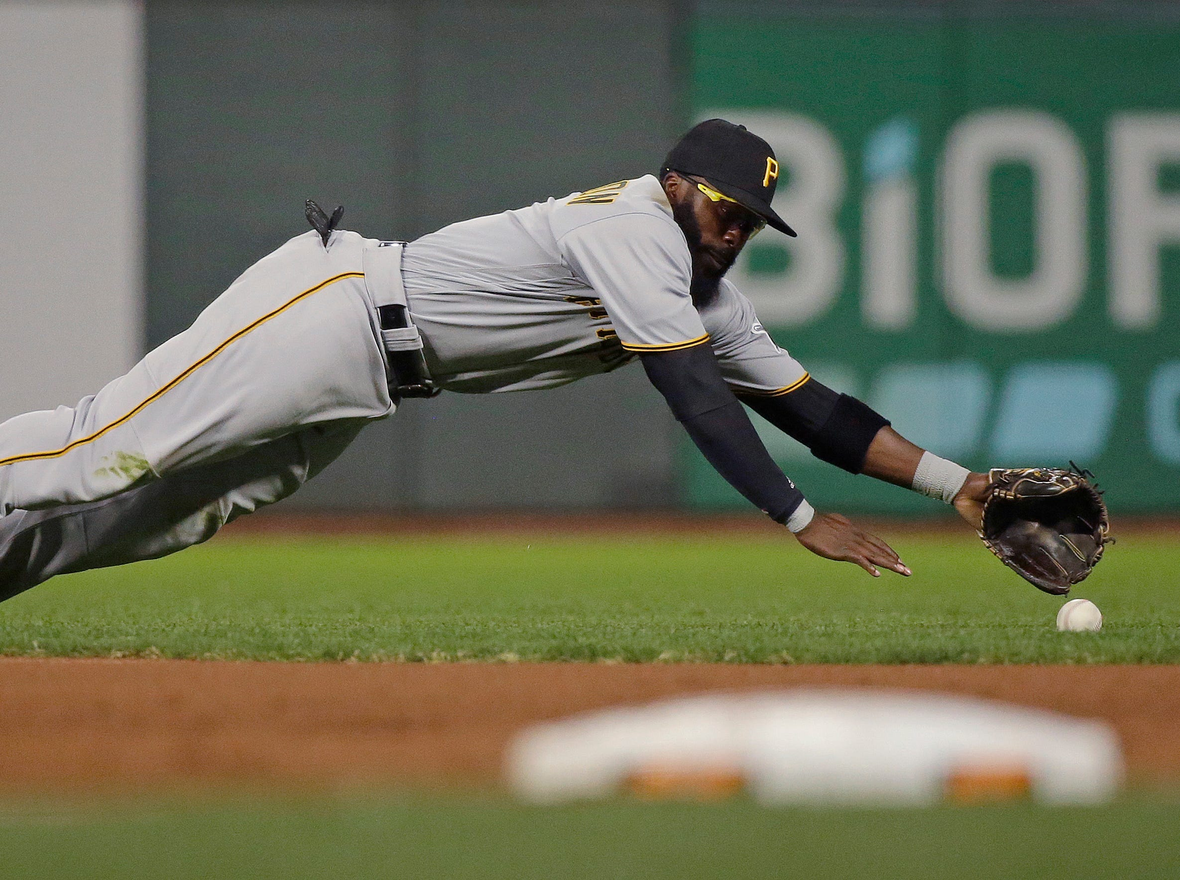 Pittsburgh Pirates second baseman Josh Harrison dives to stop a ground ball hit by San Francisco Giants' Alen Hanson during the fourth inning of a baseball game Friday, Aug. 10, 2018, in San Francisco.